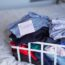 A basket of selected clothes for donating to a Charity shop on the bed. Reuse, second hand